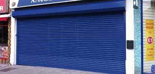Powder coated blue steel galvanised roller shutter door used to secure a large retail unit.