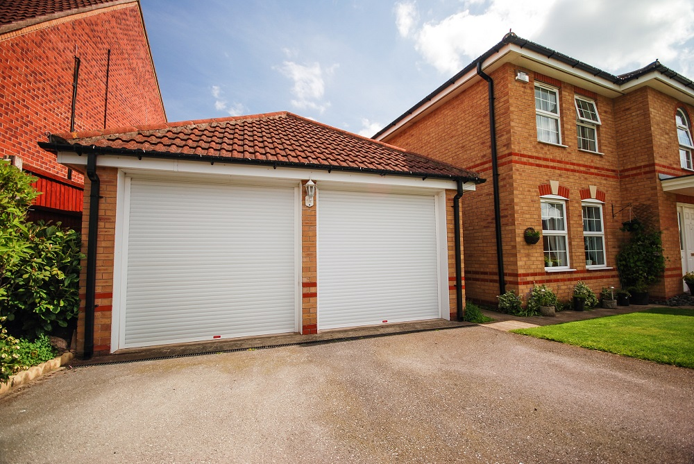 cheap insulated roller doors in white fitted side by side within a large georgian style double garage.
