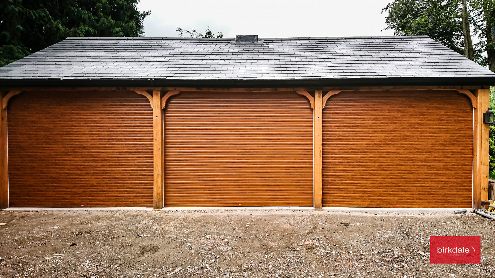 Cheap roller garage doors with a golden oak laminated finish fitted to a triple garage.